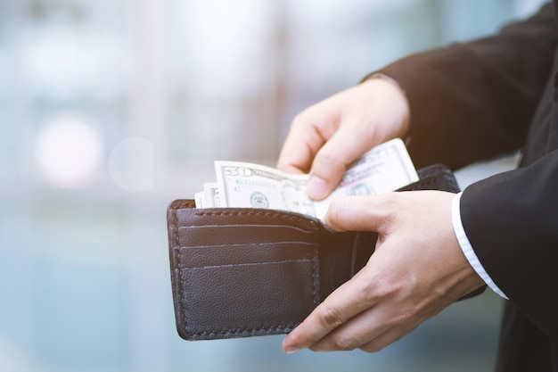 Businessman person holding an wallet in the hands of an man take money out of pocket.