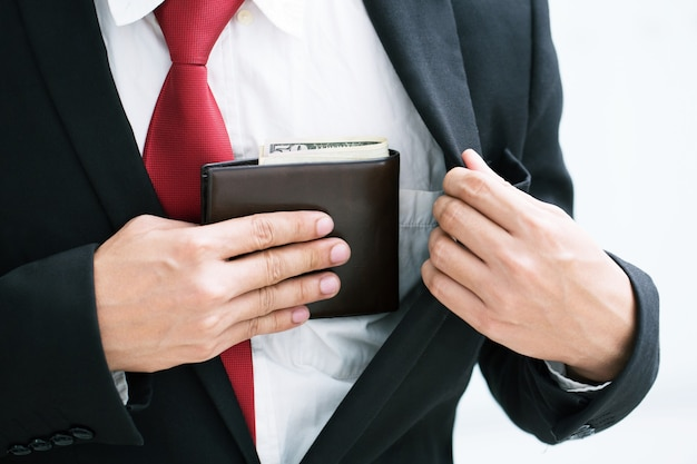 Businessman person holding an wallet in the hands of an man taking money out of his pocket.