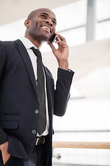 Businessman on the phone. low angle view of cheerful young african man in formalwear talking on the mobile phone and smiling