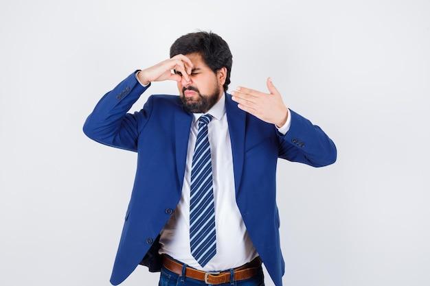 Uomo d'affari che pizzica il naso a causa del cattivo odore in abito formale e sembra tormentato, vista frontale.