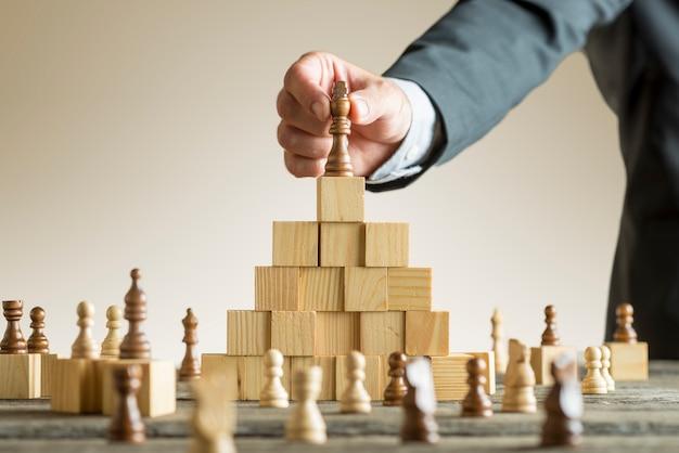 Businessman placing a chess piece on blocks