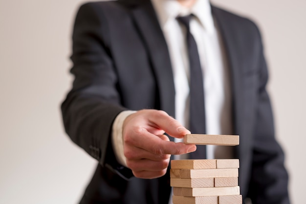 Businessman placing wooden domino in a tower