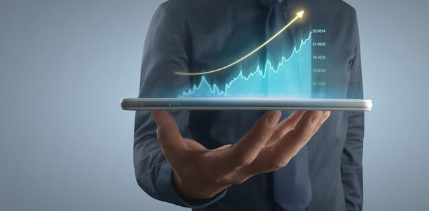 사업가 계획 그래프 성장 및 차트 긍정적 지표 증가, 손에 있는 태블릿