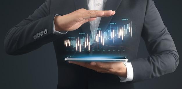 ビジネスマンは、彼のビジネスでグラフの成長とチャートの肯定的な指標の増加を計画し、タブレットを手に