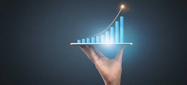 사업 계획 그래프 성장과 그의 사업에서 차트 긍정적 인 지표의 증가, 손에 태블릿
