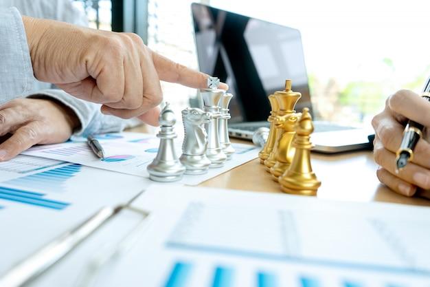 ビジネスマンがマーケティングの職場でチェスをする
