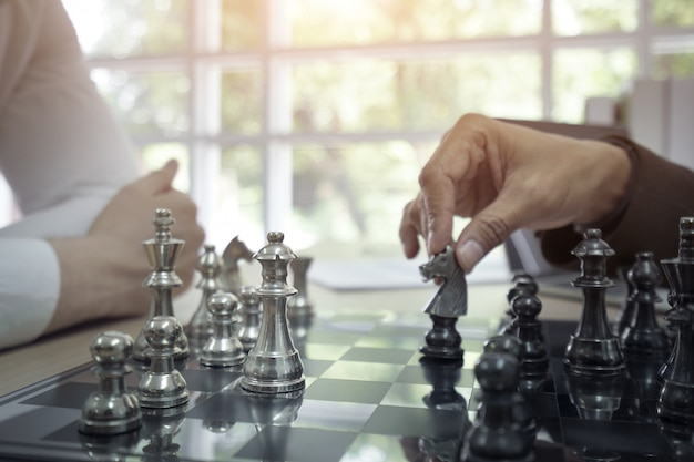 Businessman playing board chess game together.