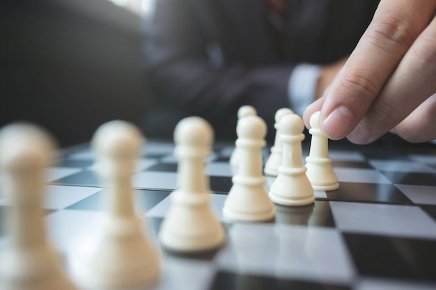 Businessman playing chess on board in office, strategy and competition concept