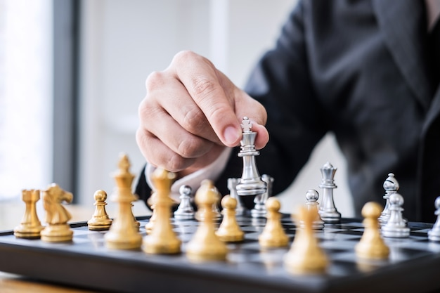 Businessman playing chess game to development analysis new strategy plan, leader and teamwork