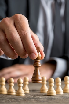 Businessman playing chess moving king piece lifting it up in a close up view