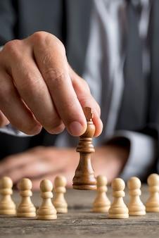 クローズアップビューでそれを持ち上げてチェスを移動キングピースを再生するビジネスマン