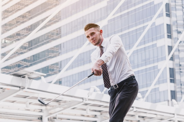 Businessman playing golf standing on the city background