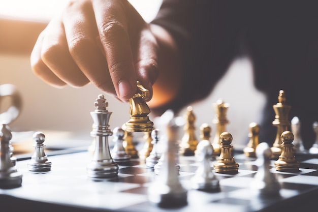 Businessman playing or moving chess figure in competition success play.