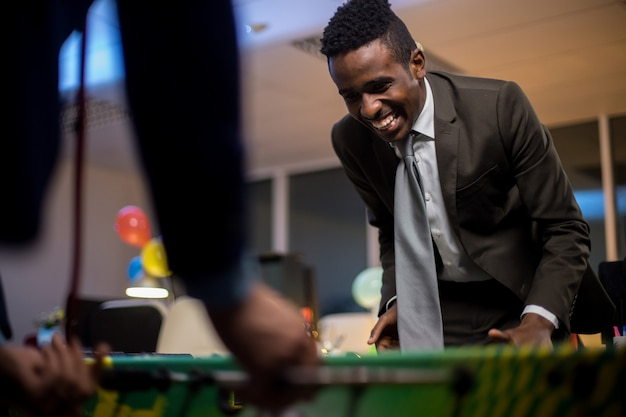 Businessman playing table football