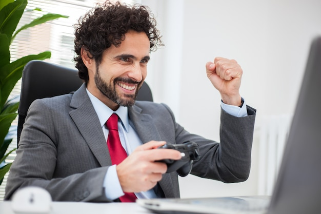 Businessman playing videogames in his office instead of working