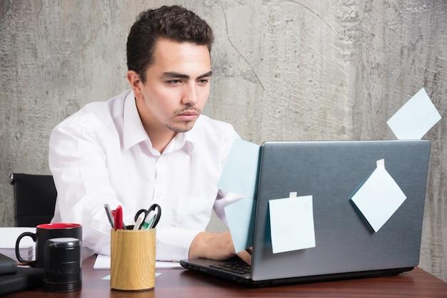 Бизнесмен, играя с ноутбуком за офисным столом.