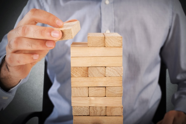 Businessman playing at a wood brick building