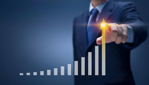 사업가는 높은 성장률로 화살표 그래프에 손을 가리킵니다. 사업가 그리기 보고서 차트를 앞으로 쇼 재무, 판매 이익, 사업 계획, 주식 시장 투자, 경제 성장 개념