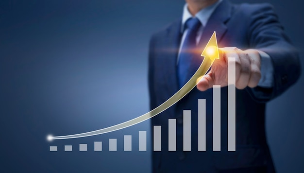 사업가는 높은 성장률로 화살표 그래프에 손을 대고 재무, 판매 이익, 사업 계획, 주식 시장 투자, 경제 성장 개념을 보여줍니다. 사업가 앞으로 보고서 차트를 그립니다