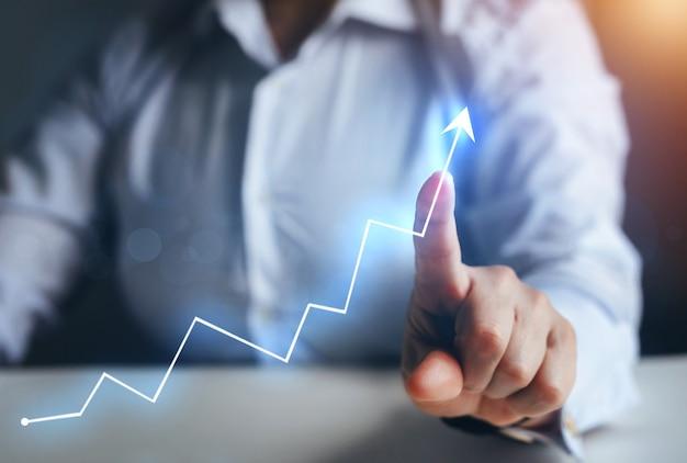 Бизнесмен, указывая стрелку графа растущее корпоративное развитие к успеху и растущему росту