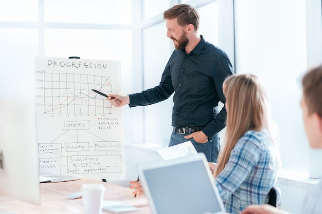 ビジネスプレゼンテーション中にグラフを指しているビジネスマン。コピースペースのある写真