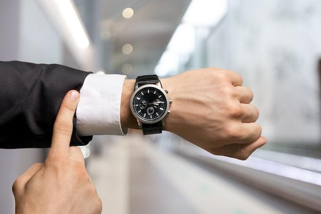 Бизнесмен, указывая на часы на сером