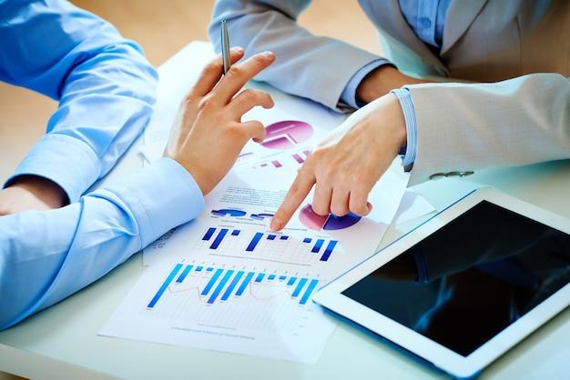 Businessman pointing a bar graph to a teamwork