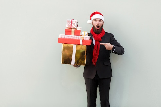 Бизнесмен, указывая пальцем на много красочных подарочных коробок и глядя с открытым ртом и большими глазами