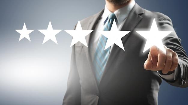 Бизнесмен, указывая символ пяти звезд, чтобы повысить рейтинг компании