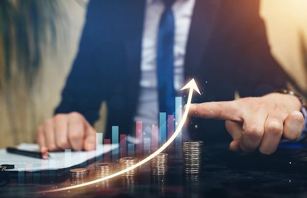 Бизнесмен указывая рост графика над стопками монет. развитие бизнеса к успеху и инвестиционный план роста.