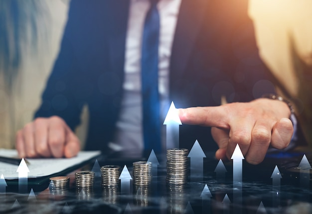 Бизнесмен указывая рост диаграммы увеличения над стопками монет. развитие бизнеса к успеху и росту прибыли.