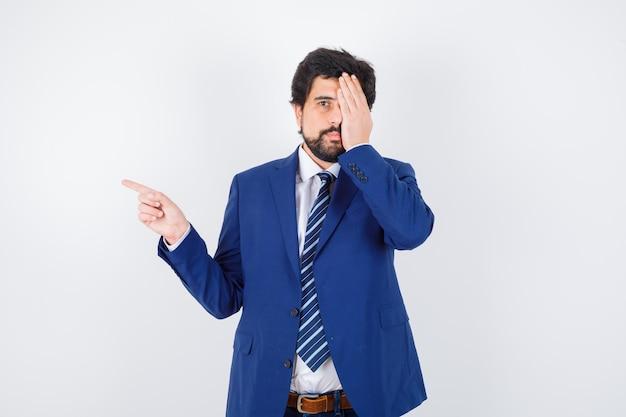Uomo d'affari che punta a sinistra con l'indice e copre l'occhio in abito formale e sembra serio, vista frontale.