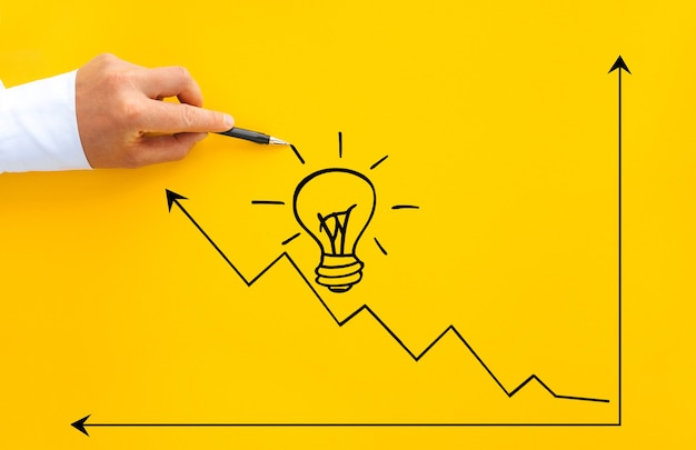 Бизнесмен указывая рост лампочки и стрелки с ручкой. цели запуска бизнеса к успеху