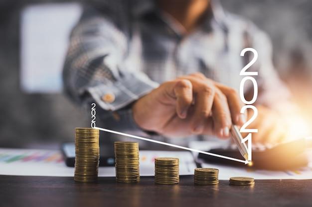 Бизнесмен, указывая на стрелку графика на стопке монет в 2021 году