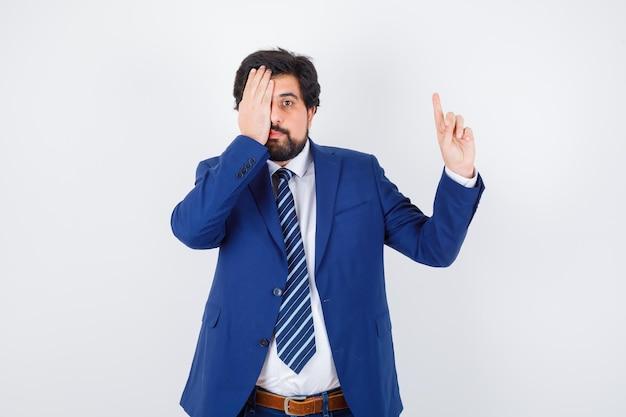 Uomo d'affari che punta a destra con l'indice e copre l'occhio in abito formale e sembra serio. vista frontale.