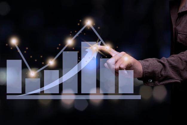 그래프 금융 차트에 사업가 포인팅 자리입니다. 디지털 비즈니스 홀로그램 그래프 금융 차트 배경입니다. 비즈니스 및 금융 개념.