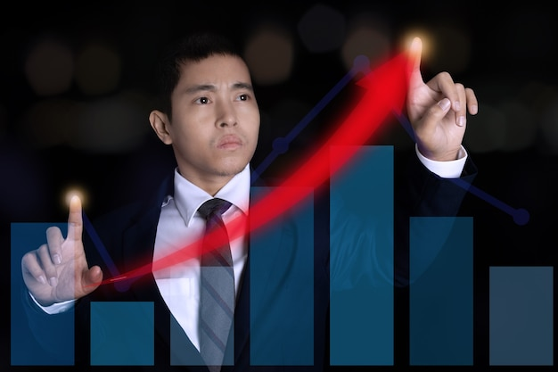 グラフ財務チャート上のスポットを指すビジネスマン。デジタルビジネスホログラムグラフ財務チャートの背景。ビジネスと金融の概念のために。