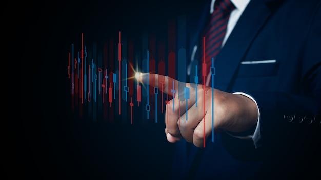 그래프 금융 차트에서 사업가 가리키는 자리. 디지털 비즈니스 홀로그램 그래프 금융 차트 배경입니다. 비즈니스 및 금융 개념입니다.