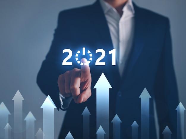 Бизнесмен, указывая кнопку старт в будущем 2021 года. развитие к успеху и концепция роста.