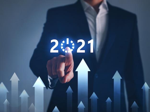 Бизнесмен, указывая кнопку старт в будущем 2021 года с цифровым графиком.