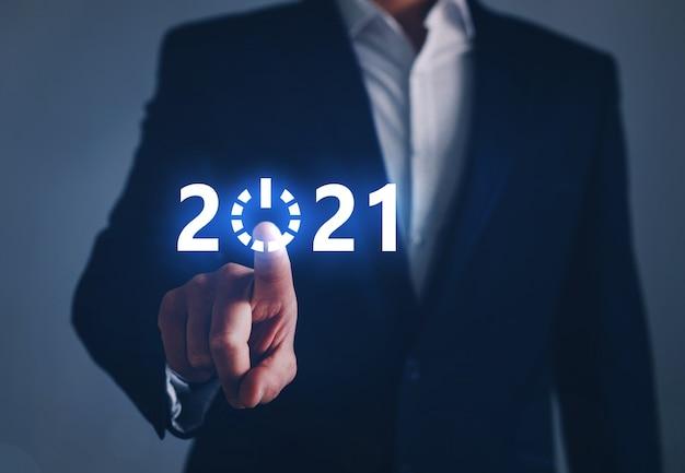 Бизнесмен, указывая кнопку старт будущего года с цифровым графиком