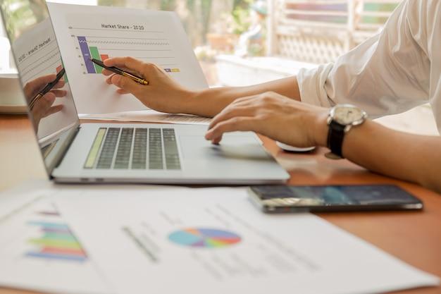 Бизнесмен указывая диаграмма графика состояния запасов с ноутбуком на столе