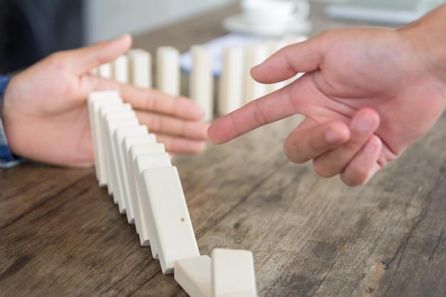 Предприниматель указывает на падающие домино и его партнера, останавливая их в концептуальном образе сотрудничества и наставника.