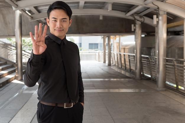 Businessman pointing up number 4 finger hand gesture