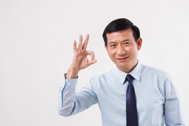 Бизнесмен, указывая вверх жест рукой ок