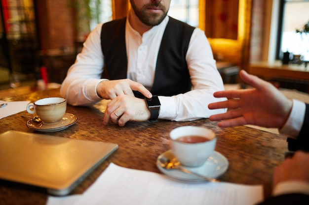 Businessman pointing at watch