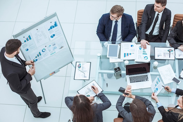 Businessman pointing with a marker on the board with the financial schedules and business team sitting on workplace