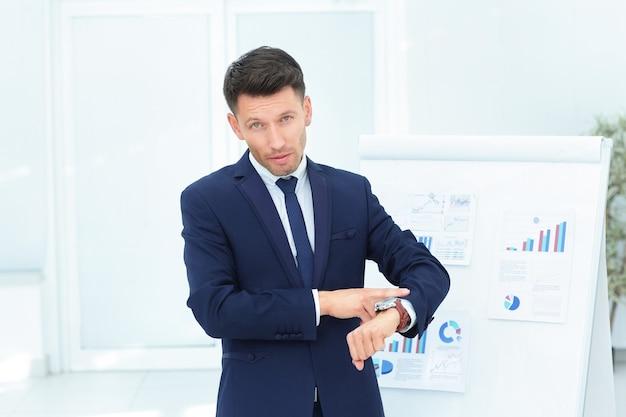 ビジネスマンは、財務スケジュールの背景に彼の時計を指しています