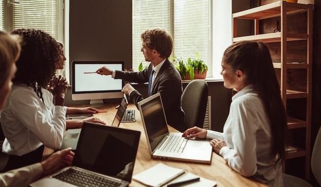 Бизнесмен указывает на белый экран монитора компьютера во время встречи молодой команды в офисе