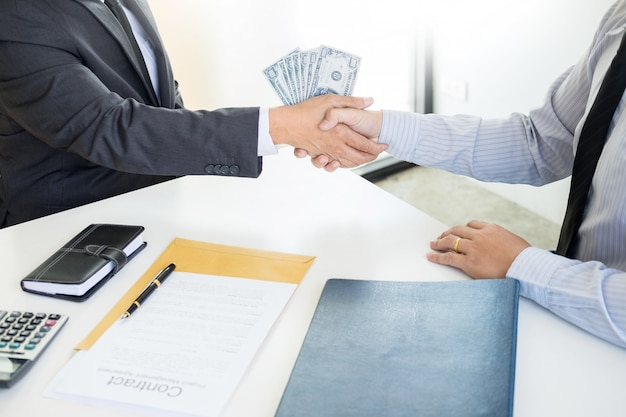 Businessman or politician taking bribe and shaking hands with money in a suit, corruption
